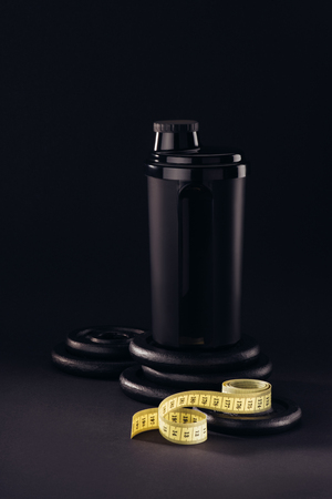 protein container with measuring tape and weight plates isolated on black