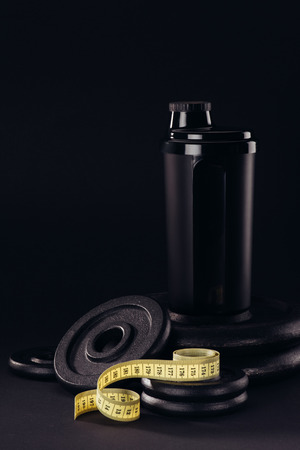 protein shaker with measuring tape and weight plates isolated on black 版權商用圖片
