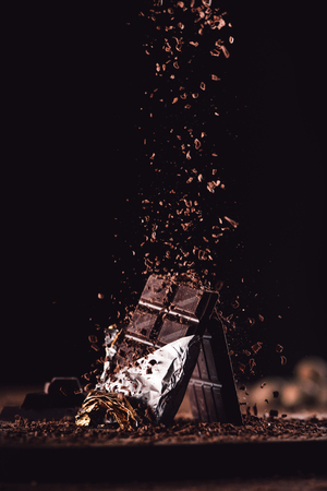 close up image of grated chocolate falling on two chocolate bars on wooden table on black background Reklamní fotografie - 106047267