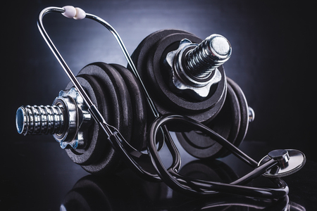 close-up view of dumbbells and stethoscope, healthy lifestyle concept