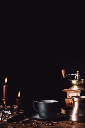 closeup shot of cup of coffee at wooden table with chocolate, truffles, coffee grains, candles and turk on black background