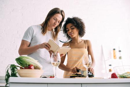 pareja interracial joven que mira la receta en el libro en la cocina