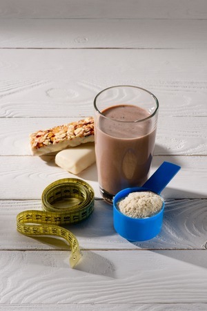 chocolate protein shake with energy bars and measuring tape on white wooden table