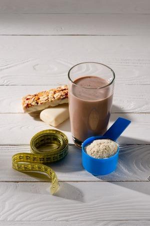 proteína de proteína de chocolate con barras de energía y cinta métrica en la mesa de madera blanca