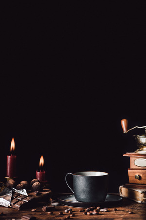 close up image of cup of coffee at wooden table with chocolate, truffles,coffee grains and candles on black background
