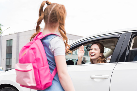 selective focus of smiling woman in car waving to daughter with backpack Stock fotó