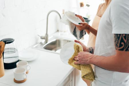 Cropped shot of man with tatoué main et petite amie laver la vaisselle dans la cuisine