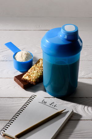 protein shaker with energy bars and measuring tape on white wooden table