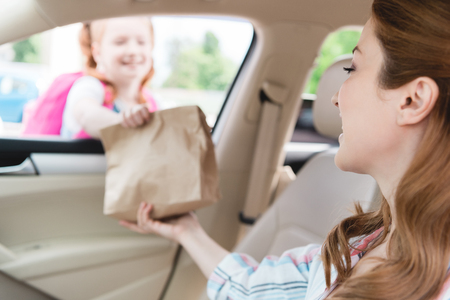 selective focus of mother in car giving paper package with food to daughter Stock Photo