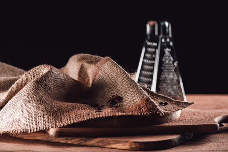 closeup image of sackcloth, grater and cutting boards on black background