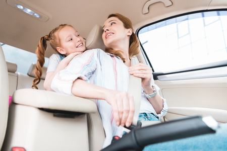 low angle view of woman fastening seat belt while driving car with daughter behind Reklamní fotografie