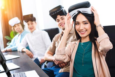 socios de negocios hispanos con auriculares virtuales de realidad en la mesa con ordenadores portátiles en la oficina moderna Foto de archivo