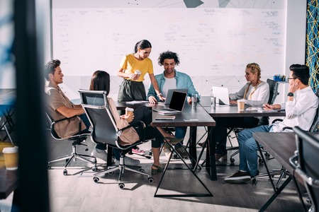 multiethnic business partners having meeting at table with laptops in modern office 스톡 콘텐츠
