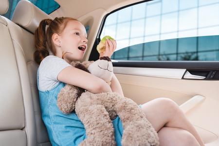 Vista lateral del muchacho emocional con el oso de peluche y la manzana fresca en el coche Foto de archivo - 106032467