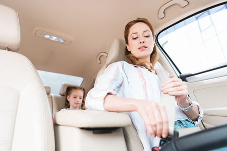 low angle view of woman fastening seat belt while driving car with daughter on passengers seat