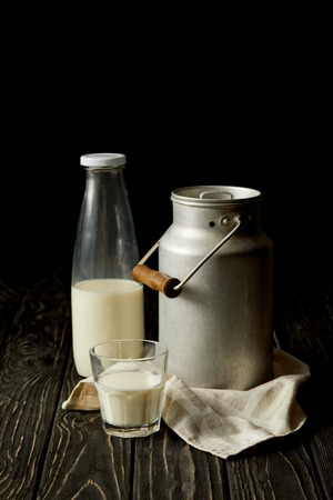 milk in bottle, glass and aluminium can on sackcloth on black background