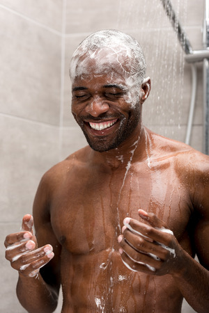 smiling young african american man washing head with shampoo in shower