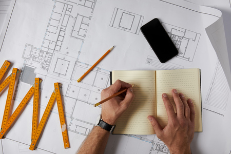 cropped image of architect writing in blank textbook on blueprint with pencil, smartphone and collapsible meter Stock fotó
