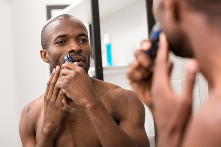 attractive young man shaving beard with electric shaver while looking at mirror in bathroom
