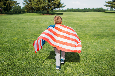 back view of little boy with american flag running on grass Stock Photo