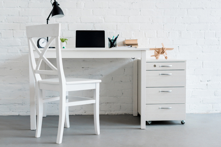 modern work desk with laptop at home in front of white brick wall 스톡 콘텐츠