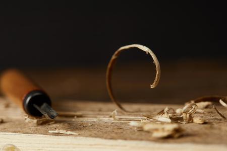 close-up weergave van beitel en houten scobs op onscherpe zwarte achtergrond