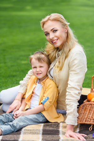 happy mother and son smiling at camera while sitting together on plaid at picnic