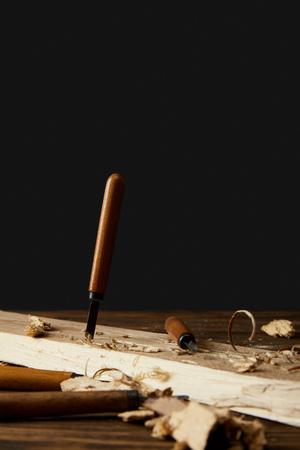 Cincel cortado en la madera en la mesa sobre fondo negro Foto de archivo - 106066850