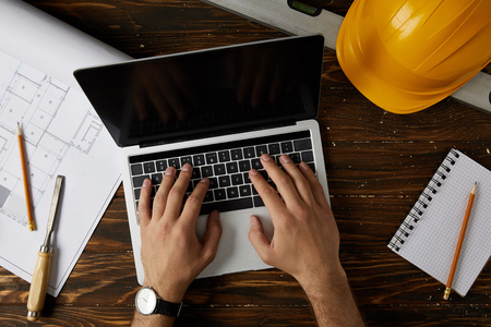 cropped image of architect typing on laptop at table with chisel, spirit level, protective helmet, blueprint, textbook and pencils Stock Photo