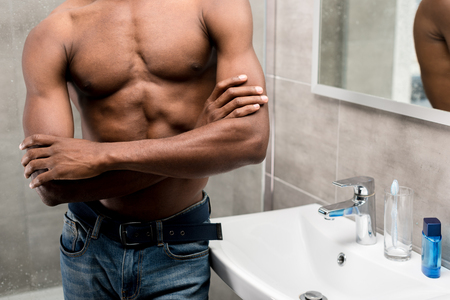 cropped shot of young african american man standing with crossed arms in bathroom
