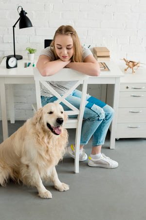 smiling teen girl spending time at home with her dog Banque d'images - 106067152