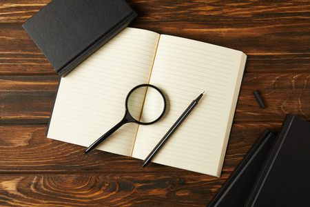 top view of magnifying glass, notebooks and pen on wooden table