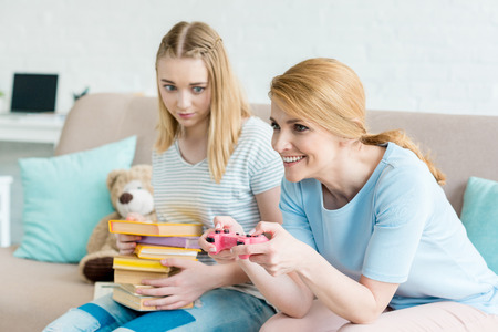 mother playing console game while her confused daughter sitting with stack of books on couch Stock Photo