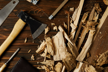 axe, chisel, handsaw and wooden pieces on brown tabletop