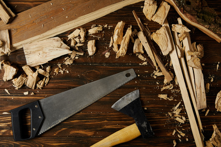 elevated view of axe, handsaw and wooden pieces on brown table
