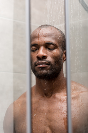 handsome young african american man standing with closed eyes in shower 版權商用圖片 - 106067902