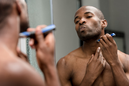 cropped shot of young african american man shaving with electric trimmer and looking at mirror Фото со стока