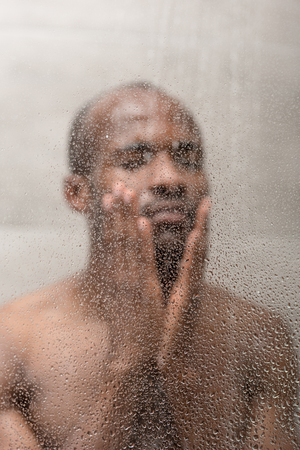 selective focus of handsome young african american man washing in shower 版權商用圖片