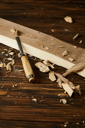 close up image of chisel and wooden pieces on brown table