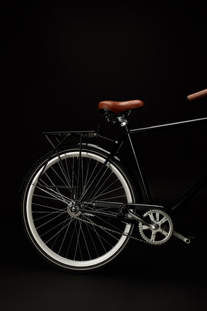 saddle, wheel and pedals of vintage bicycle isolated on black