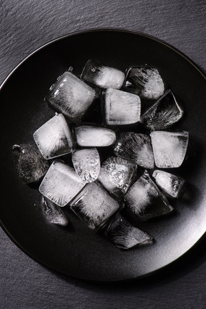 Ice cubes melting in black plate on dark background 写真素材