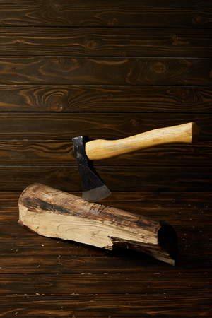 close up shot of sticking axe in log on brown wooden surface Imagens
