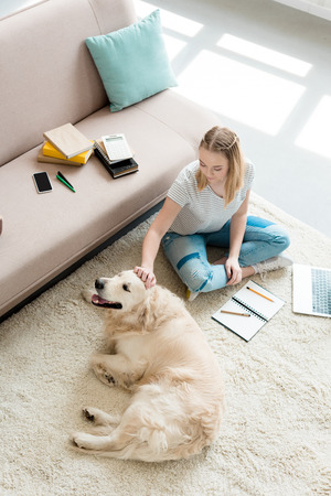 high angle view of beautiful teen girl petting her dog while doing homework Banque d'images - 106070058