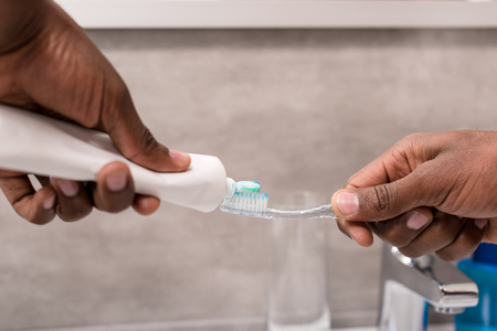 cropped shot of man applying toothpaste onto brush