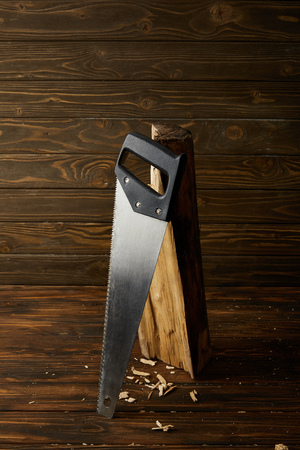 closeup view of handsaw and log on wooden brown table