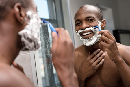 handsome smiling african american man shaving and looking at mirror