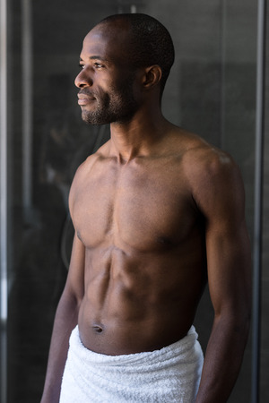 handsome bare-chested african american man in towel standing and looking away in bathroom 版權商用圖片 - 106070614