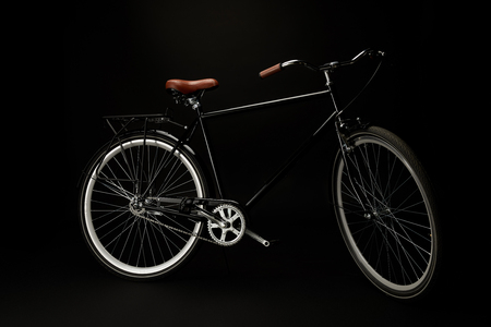 side view of comfortable vintage bicycle isolated on black Banco de Imagens