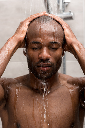 handsome young african american man washing in shower with closed eyes