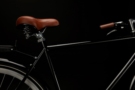 close-up view of saddle and handlebar of classic bicycle isolated on black